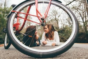 photo showing two people and bicycle