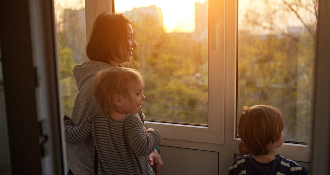 photo of woman and children looking out of a window