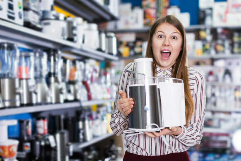 Electrical appliance recyclin is getting easier: Woman in electrical store holding food mixer
