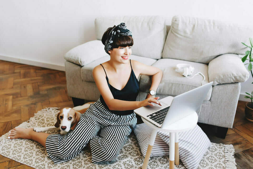Woman using recycling locator on her laptop with dog by her side, making use of tools available for recycling electronics