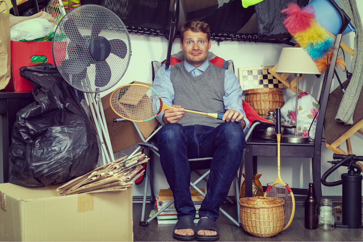 man in garage with hoarded items