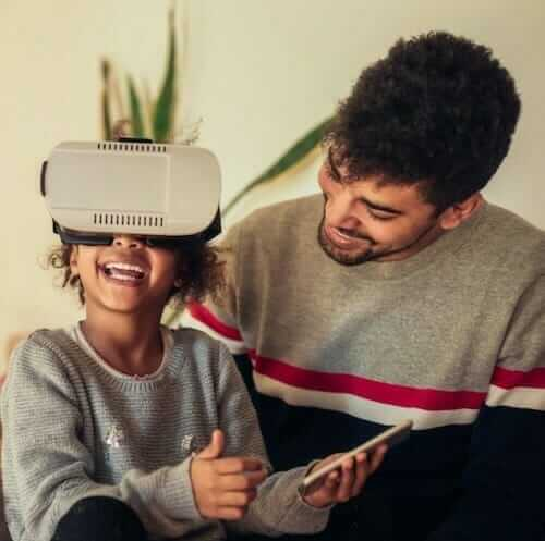 child with VR headset and adult