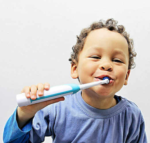 child using electrical toothbrush