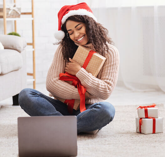 Woman with laptop holding christmas gif